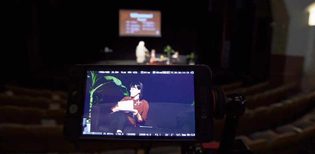 En kameramonitor filmar en scen med människor på